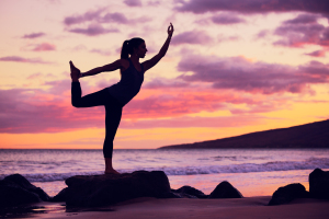 Woman practicing yoga on the beach at sunset